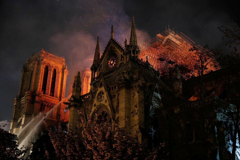 Los bomberos continuan luchando durante la noche contra las llamas para salvar a la catedral.