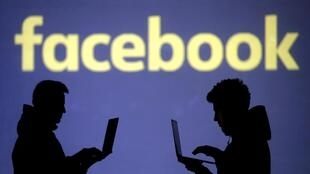 Silhouettes of laptop users are seen next to a screen projection of Facebook logo in this picture illustration taken March 28, 2018.