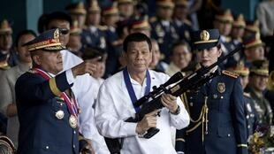 Le président philippin, Rodrigo Duterte, tient un fusil de tireur d'élite Galil avec le chef sortant de la Police nationale philippine (PNP), Ronald dela Rosa, lors de la cérémonie de passation du commandement au camp Crame à Manille le 19 avril 2018.