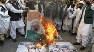 Manifestantes queimam bandeira com foto representando premiê indiano Narendra Modi durante protesto no Paquistão sobre situação da Caxemira