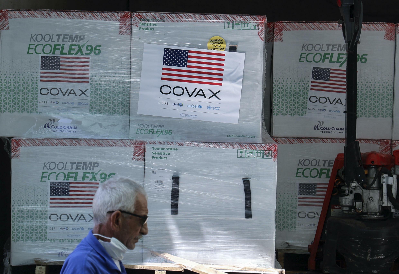 Un empleado del Ministerio de Sanidad palestino pasa frente a un cargamento de 300.000 dosis de vacunas contra el coronavirus enviadas por UNICEF mediante la iniciativa Covax, el 24 de agosto de 2021 en Salem, cerca de la ciudad cisjordana de Naplusa