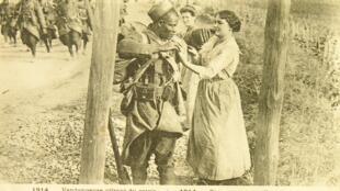 Une vendangeuse offrant du raisin à un blessé sénégalais en 1914.