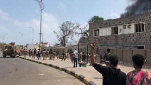 Des forces de sécurité yéménites et des habitants d'Aden observent le lieu d'une attaque suicide à la voiture piégée, le 5 novembre 2017.