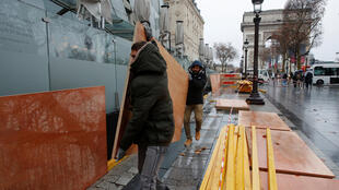 """Lojistas da avenida Champs Elysées protegem suas vitrines com tapumes para evitar depredações durante manifestação dos """"coletes amarelos""""."""
