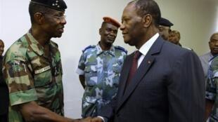 O presidente marfinense Alassane Ouattara cumprimenta o general Philippe Mangou no Hotel do Golfe de Abidjã a 12 de Abril de 2011.