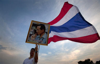 A government supporter on Sunday's demonstration holds a portrait of King Bhumibol Adulyadej