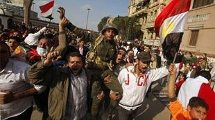 Demonstrators carry a soldier on his shoulders near Tahrir Square in Cairo