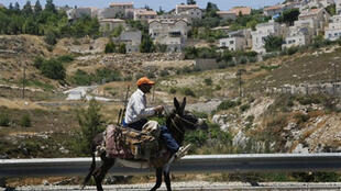 Un Palestinien passe devant une colonie juive en Cisjordanie à Elazar à 20 km au sud de Jérusalem, le 19 juin 2009.