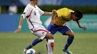 O jogador Felipe Amorim, do Brasil, disputa bola com Joseph Mora de Costa Rica.