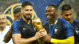 France's Olivier Giroud and Steve Mandanda celebrate with the trophy after winning the World Cup