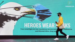 Homem caminha diante de um anúncio que pede o uso de máscaras, em Melbourne, Australia.