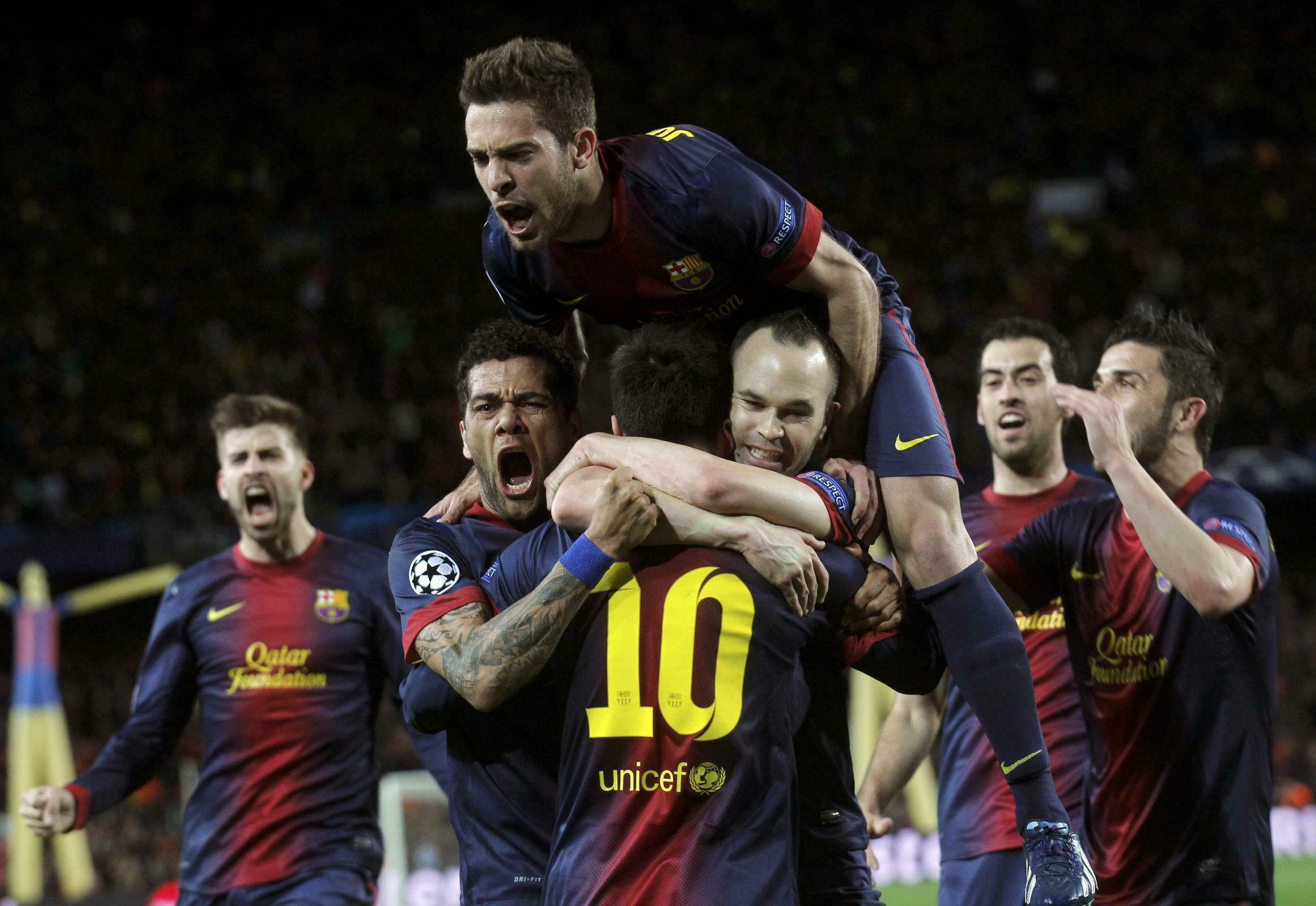 Barcelona's Lionel Messi (10) is congratulated by his team after scoring his second goal against AC Milan, 12 March, 2013