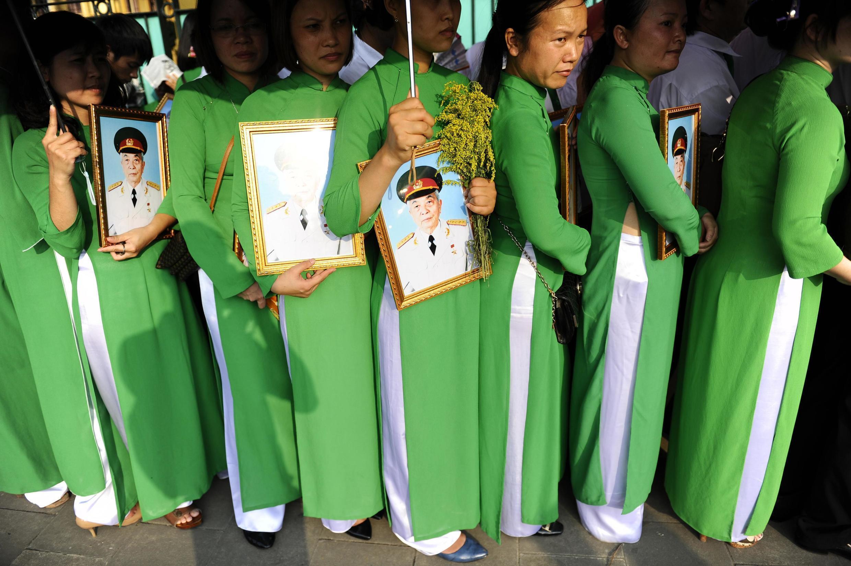 Tại Hà Nội, phụ nữ mang ảnh Tướng Giáp sắp hàng chờ vào viếng người quá cố. Ảnh chụp ngày 10/10/2013.
