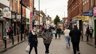 Peatones llevan mascarillas debido a la pandemia del nuevo  coronavirus, caminan por High Street de Leigh, Greater Manchester, al noroeste de Inglaterra, el 22 de octubre de 2020, cuando se imponen en el Greater Manchester nuevas restricciones para contener los casos de Covid-19
