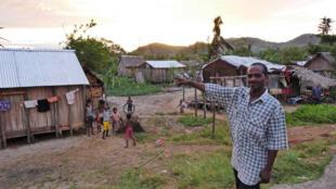Jean-Chry, chef de quartier à Ampahana, montre les nouveaux toits en taule des maisons de son quartier.