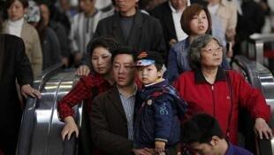 Un hombre lleva un niño junto a su mujer en el metro de Shanghai, el 28 de abril de 2011.