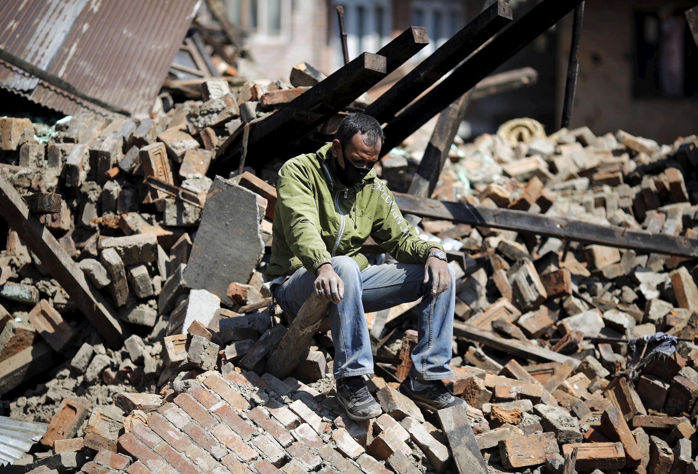 Một người dân ngồi giữa đống đổ nát của nhà mình tại Katmandou, Népal  sau trận động đất hôm 25/04/2015.