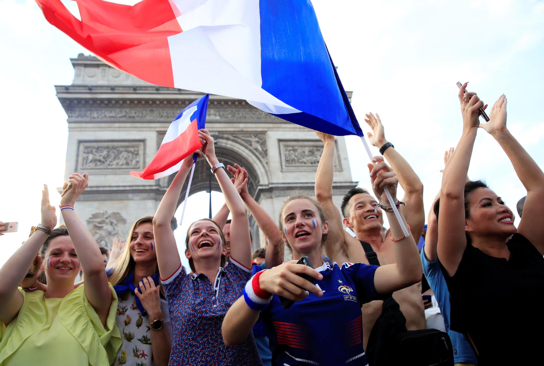 Thanh niên Pháp trước Khải Hoàn Môn chào mừng chiến thắng của đội bóng Áo Lam. Ảnh ngày 15/07/2018.
