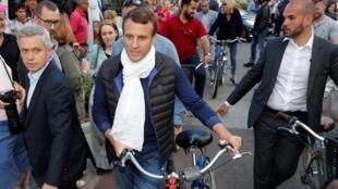Shugaban kasar Faransa Emmanuel Macron tare da matarsa Brigitte Trogneux a kan kekuna, yayinda al'ummar kasar ke dunguma zuwa rumfunan zabe don kada kuri'unsu a zagayen farko na zaben 'yan majalisar kasar.