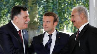 Waziri Mkuu wa Libya Fayez al-Sarraj (kushoto) na Jenerali Khalifa Haftar, kiongozi wa kikosi kinachoitwa Jeshi la Taifa la Libyan (ANL), wakisabahiana mbele ya Rais wa Ufaransa Emmanuel Macron huko Celle-Saint-Cloud, karibu na Paris, Julai 25, 2017.