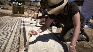 An archaeologist works on a mosaic on the antiquity site of Sainte-Colombe, near Vienne.