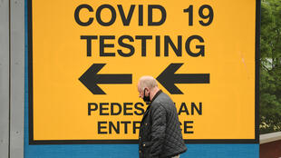 A pedestrian in the city of Bolton, in northwest England, walks past a sign pointing to a Covid-19 testing center on May 28, 2021
