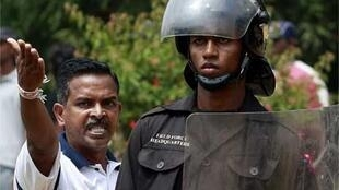 A supporter of President Rajapakse with a riot police officer at the Colombo clashes