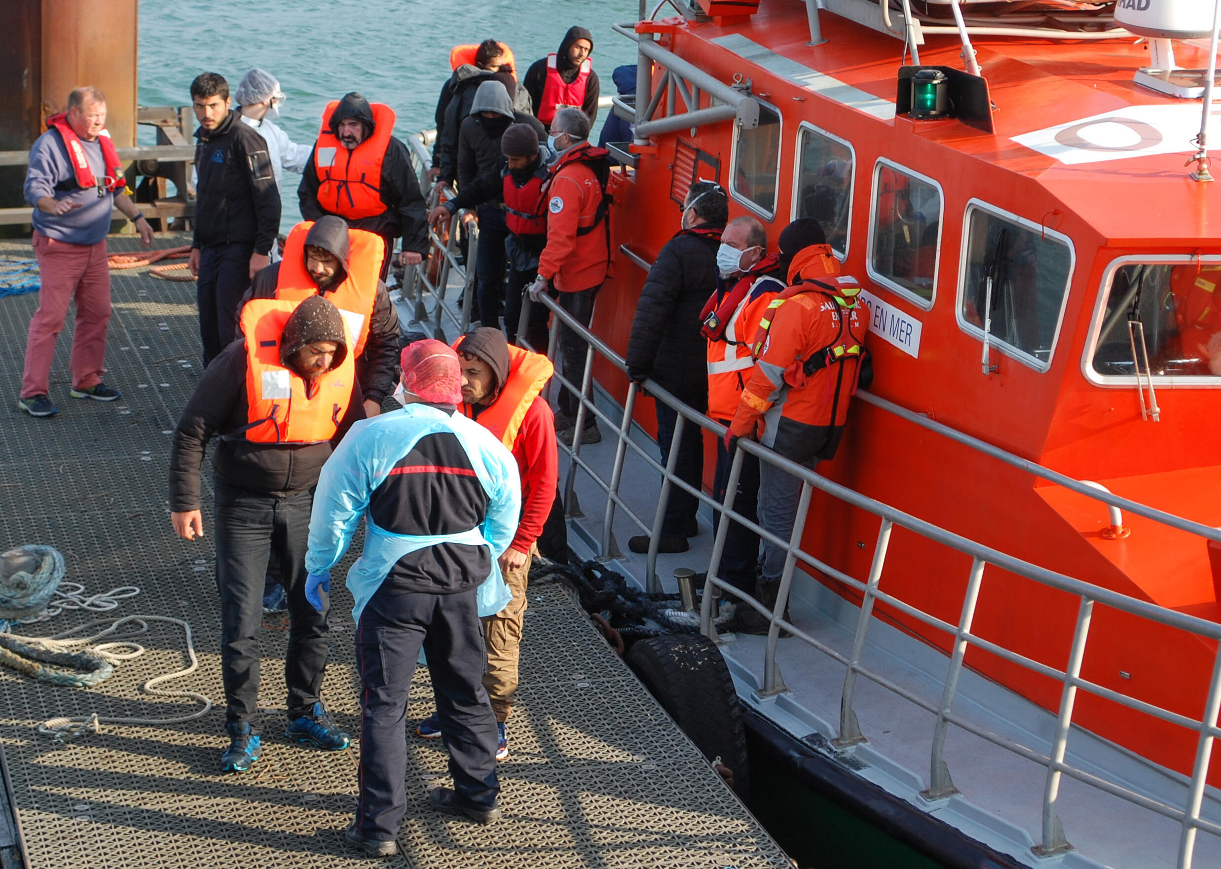 This April 2020 file photo shows Migrants getting off a rescue boat after being rescued along the French coast while trying to cross the Channel to the UK.