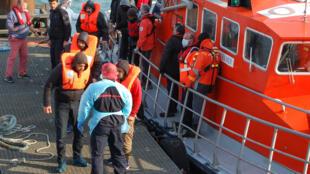 Migrantes à saida de um barco de socorro em Calais