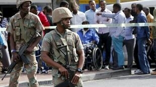 Soldiers stand guard as police conduct a raid in Cape Town