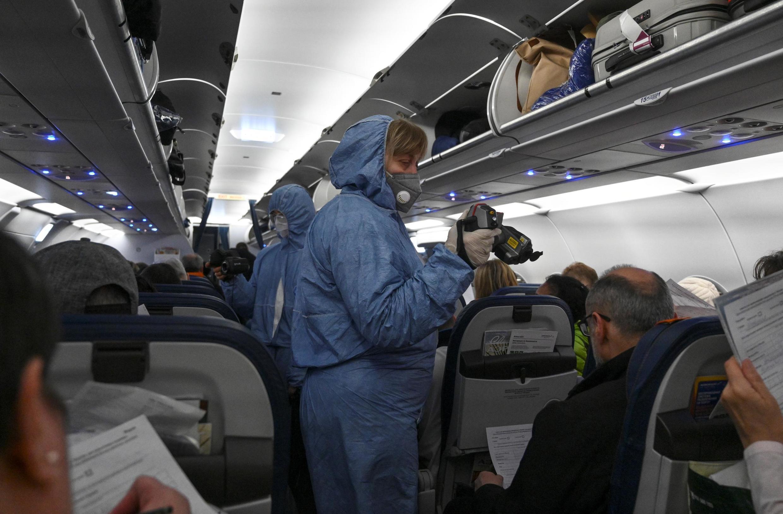 Медики проверяют температуру у пассажиров самолета в Шереметьево. 18 марта 2020 г.