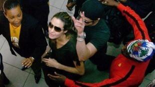 Le couple d'acteurs américains, Angelina Jolie et Brad Pitt (c), et le rappeur américain, Wyclef Jean (d), à l'aéroport Toussaint Louverture de Port-au-Prince, le 13 janvier 2006.