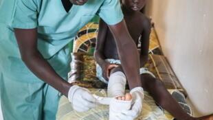 Aluk Manut, de 6 años fue mordida en el pie por una serpiente. Un enfermero MSF se ocupa de ella en el hospital de Agok, en Sudán del Sur. Ella y su madre tuvieron que recorrer 150 km. para llegar hasta Agok.