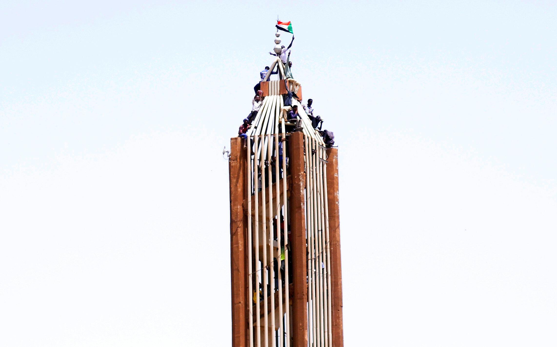 Des manifestants soudanais sur le toit d'un bâtiment à proximité du ministère de la Défense, le 11 avril 2019.