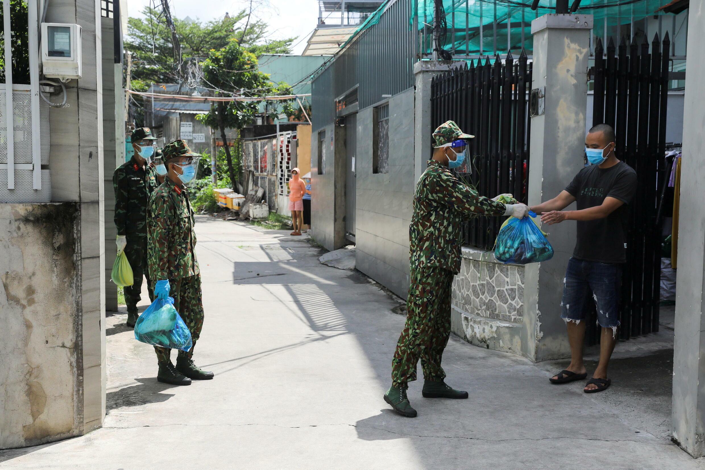 """Chủ trương bộ đội """"đi chợ"""" cho dân Sài Gòn trong thời gian siết chặt phong tỏa thất bại, sau vài ngày đầu thực hiện. Trong ảnh, cảnh bộ đội trao thực phẩm cho dân, TP Hồ Chí Minh, ngày 24/08/2021."""