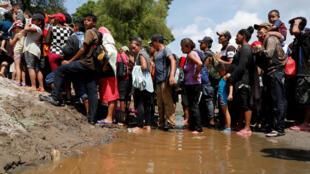 پناه جویانی که رودخانۀ سوچیاته را پشت سر گذاشته و در انتظار عبور از تپههای کنار آن هستند تا وارد خاک مکزیک شوندتا به مکزیک