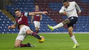 El delantero brasileño del Manchester City Gabriel Jesús (D) remata sobre la portería del Burnley, ante la marca del defensa James Tarkowski (I), en partido de la Premier League jugado el 3 de febrero de 2021 en Burnley