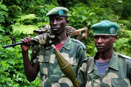 Deux hommes membres du mouvement rebelle M23 patrouillent dans une zone du Nord-Kivu.