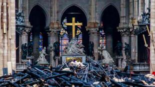 Vue de la croix et de la sculpture de Nicolas Coustous au milieu des débris à l'intérieur de la cathédrale Notre-Dame de Paris. Photo prise le jour après l'incendie du 15 avril 2019.