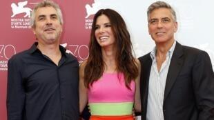 Le réalisateur du film «Gravity» Alfonso Cuaron (g) et ses deux comédiens, Sandra Bullock (c) et George Clooney (d), à la 70e Mostra de Venise, le 28 août 2013.