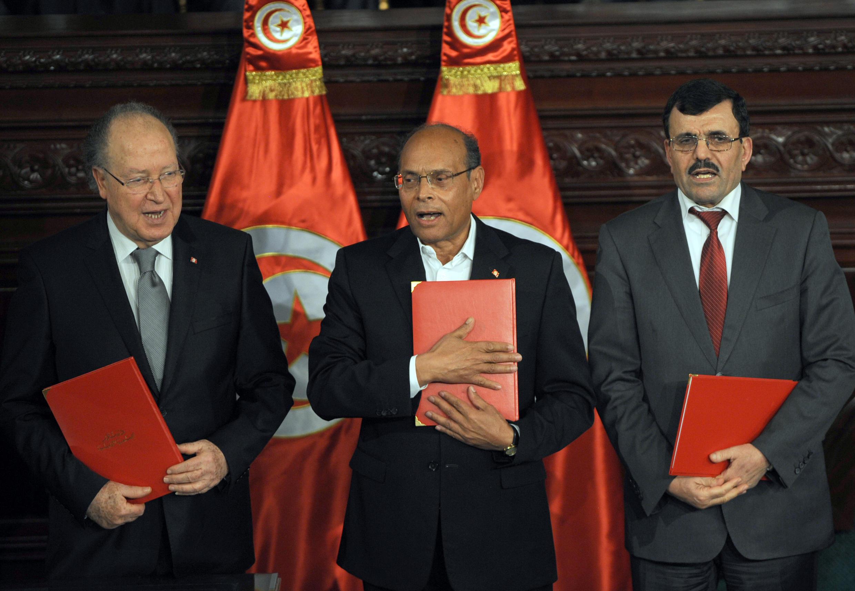 Le président de la République (c), le président de l'Assemblée nationale (g)et le Premier ministre sortant  lors de la cérémonie de signature de la Constitution, Tunis, le 27 janvier 2014.