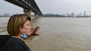 Unos habitantes de Wuhan, en la provincia central china de Hubei, observan la crecida del río Yangtsé el 14 de julio de 2020