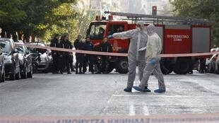 Police experts search for evidence outside the courier company where the package exploded in Athens