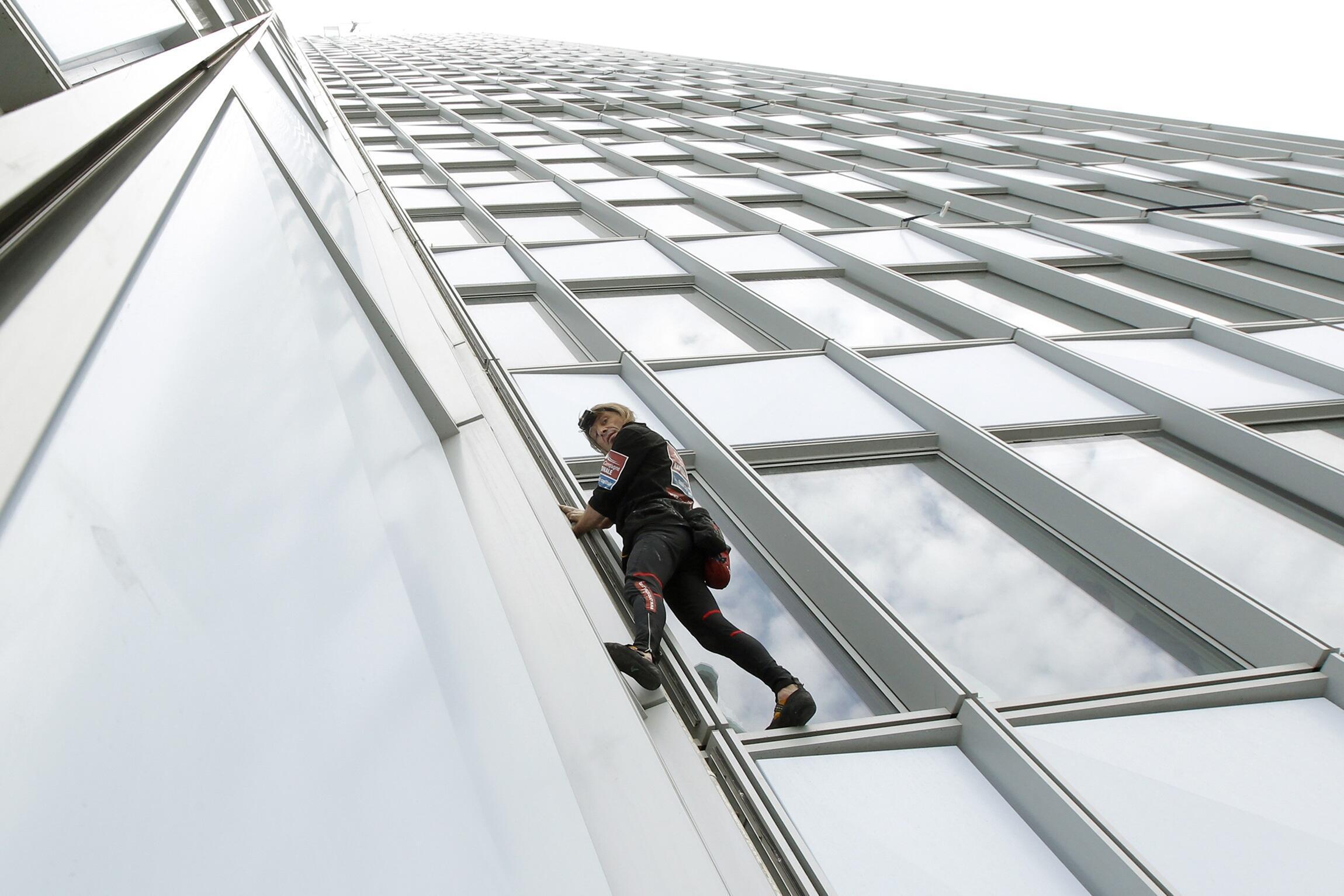 Alain Robert grimpant la tour First à la Défense, le 10 mai 2012.