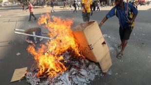 Les partisans du parti d'opposition, le Mouvement pour le changement démocratique (MDC), mettent le feu aux cartons et aux ordures lors des manifestations sur les résultats des élections à Harare, au Zimbabwe, le 1er août 2018.