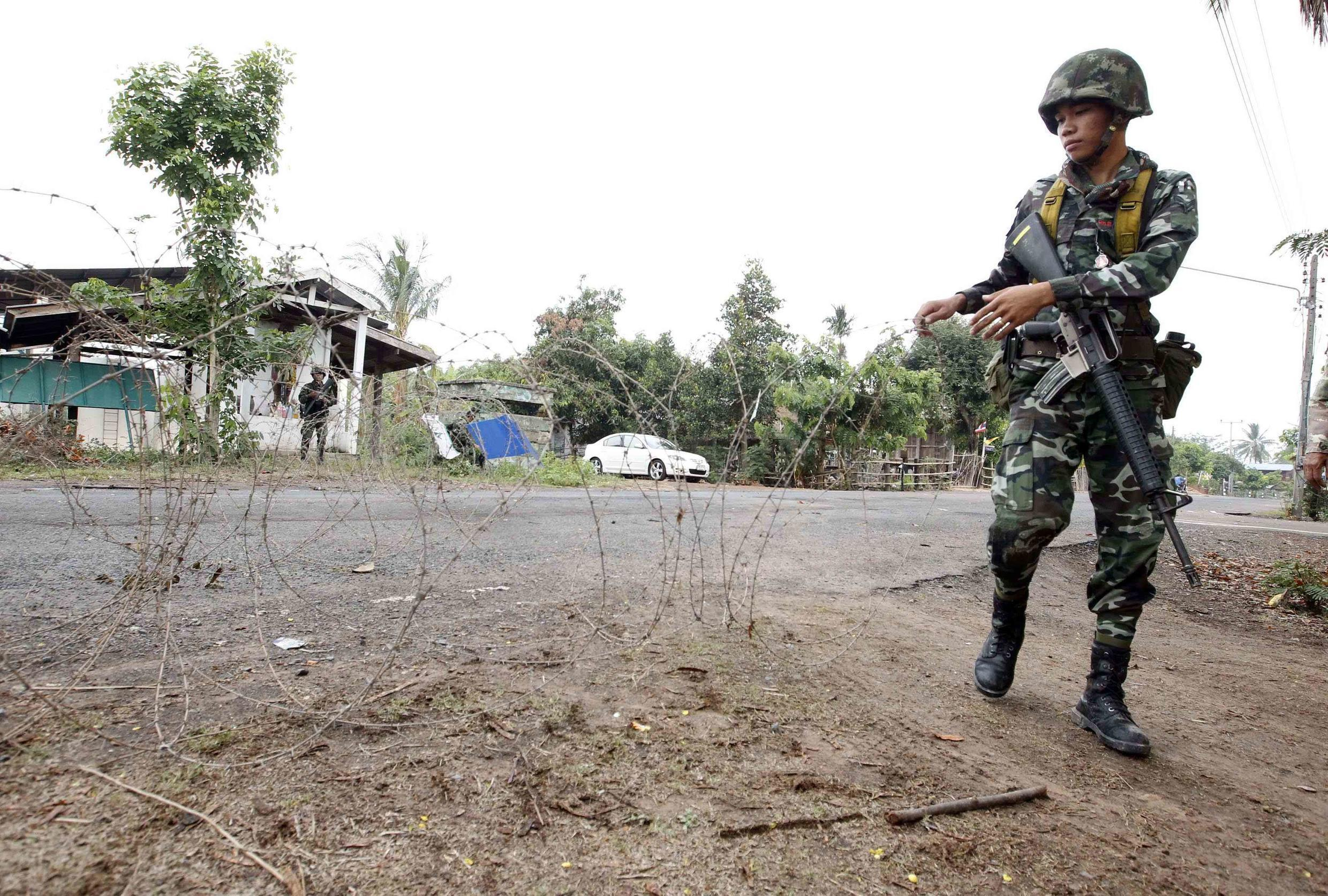 A Thai soldier mans a razor-wire roadblock close to the Thai-Cambodia border shortly before fighting erupted for a third day