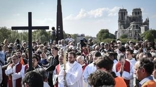 Des fidèles assistent à la cérémonie du chemin de croix pendant le Vendredi saint dans le cadre des célébrations de la Semaine sainte, près de la cathédrale Notre-Dame, le 19 avril 2019.