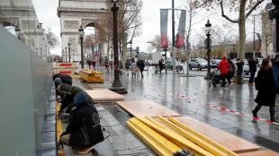 Des ouvriers installent, le vendredi 7 décembre 2018, des planches pour protéger une vitrine d'un magasin sur les Champs-Elysées, près de l'Arc de Triomphe, à la veille de «l'acte IV» des «gilets jaunes».