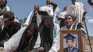 People stand next to a mass grave containing the bodies of 81 victims of Eritrean and Ethiopian forces in the city of Wukro in the Ethiopian region of Tigray on February 28, 2021