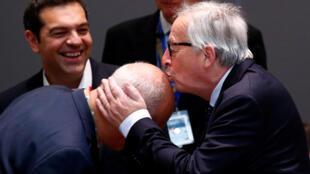 ژان کلود یونکر رئیس کمیسیون اروپا از خوشحالی امضای توافق سر یکی از همکارانش را میبوسد. تسیپراس نخست وزیر یونان در عکس دیده میشود